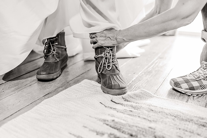 a black and white photo of a bride wearing duck boots under her wedding dress