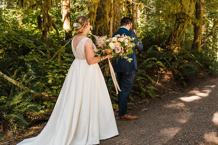 a bride in the forest holding her bouquet and approaching her groom from behind for a first look
