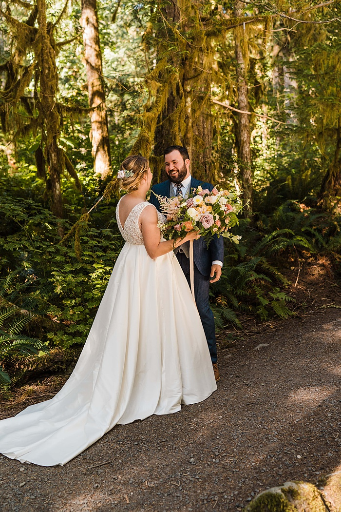 a bride and groom having their first look in the forest