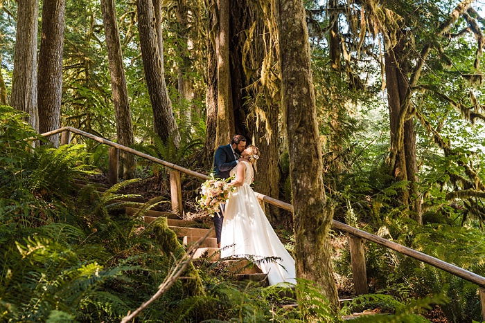a bride and groom embracing in a forest setting