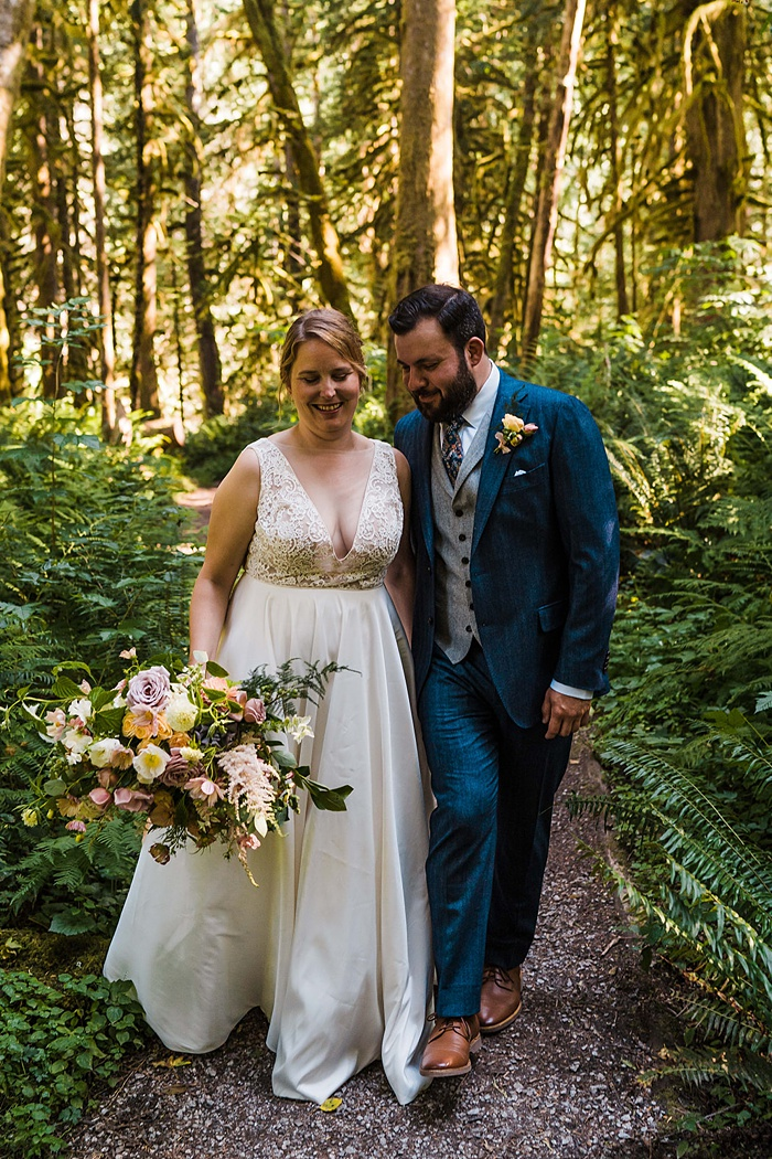 a bride and groom walk together in the woods, holding the bridal bouquet