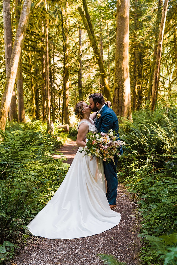 a bride and groom kissing in the forest