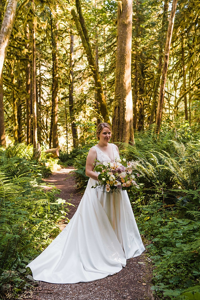 a bride walks through the forest with her summer bouquet