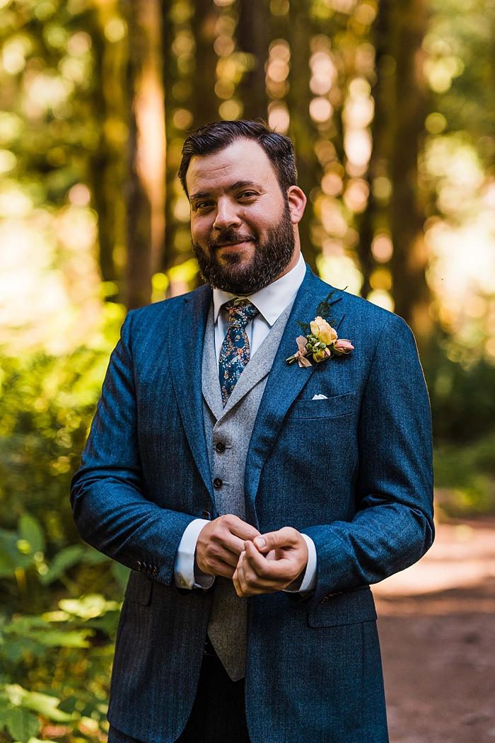 a groom adjusts his cufflinks in the woods while he waits for his bride