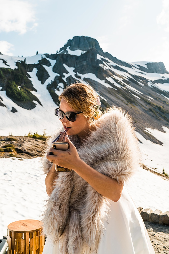 a bride in a fur wrap at a mountain summit with snow in the background, with sunglasses on and applying lipstick