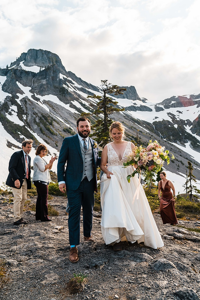 a bride and groom walk away from the mountain wedding ceremony, newly married!