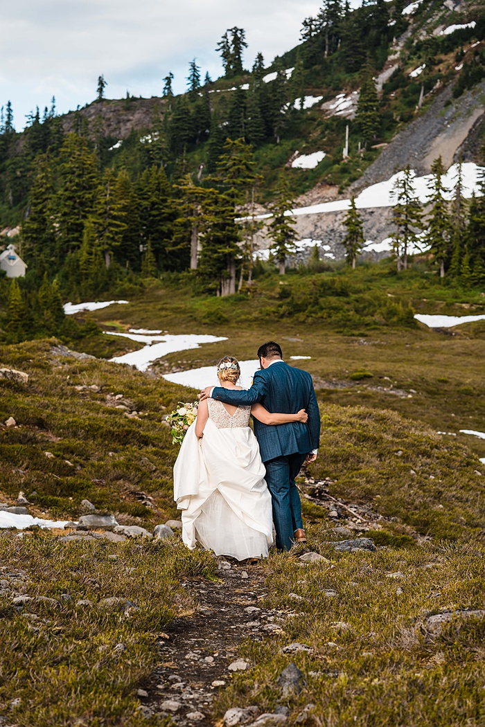 the bride and groom hiking to their next mountain elopement destination