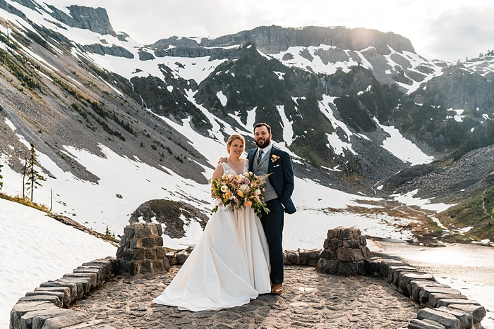 a bride and groom stand together smiling with a mountain backdrop