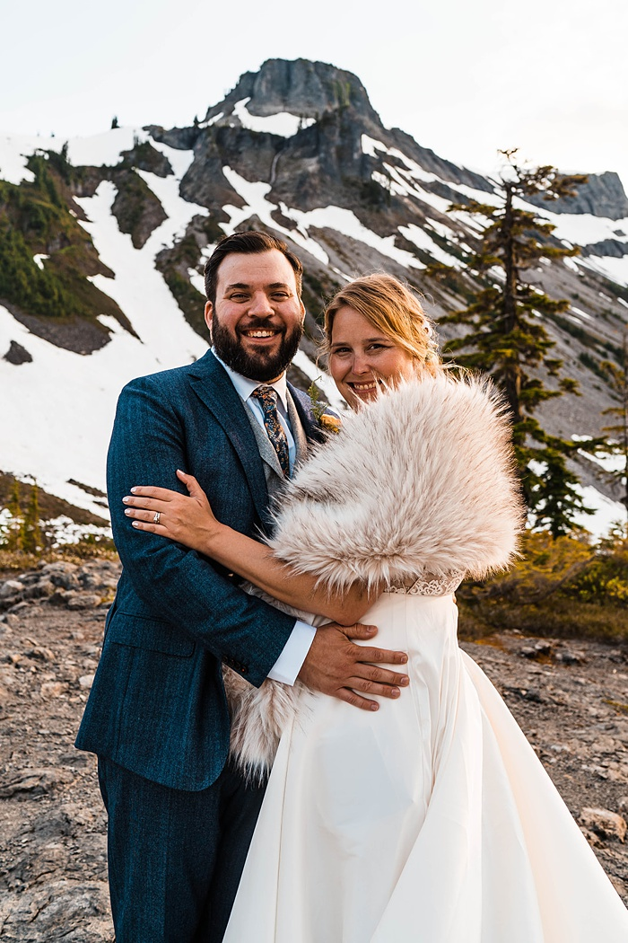 a bride and groom embracing on a mountaintop smiling