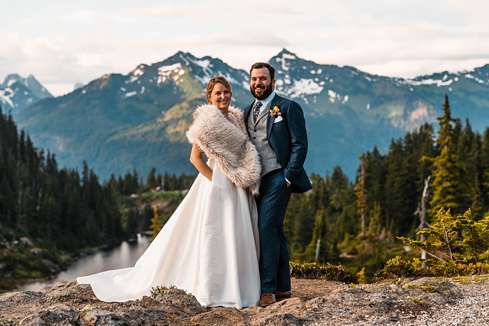 a bride and groom stand on a mountaintop, smiling after celebrating their elopement