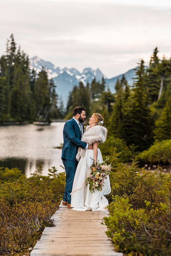 a bride and groom walk together on a trail in front of a mountaintop lake, celebrating their elopement