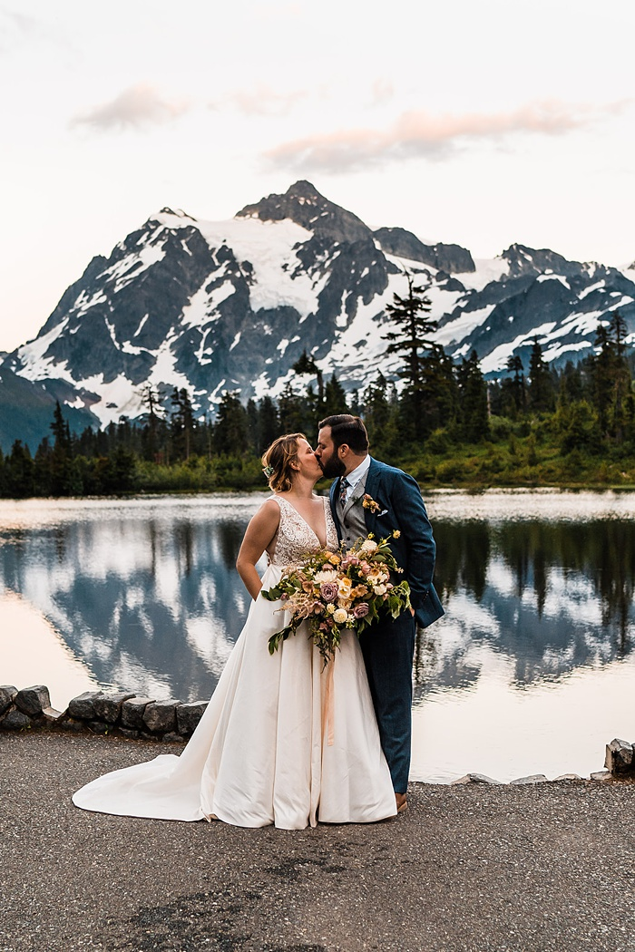 a bride and groom embrace in front of a mountainside lake