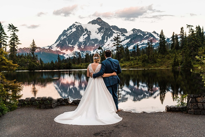a bride and groom embrace in front of a lake at sunset, with a mountain in the background