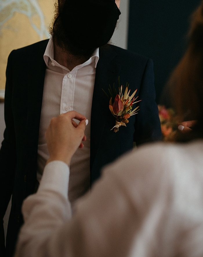 mom pins a boutonniere on the groom