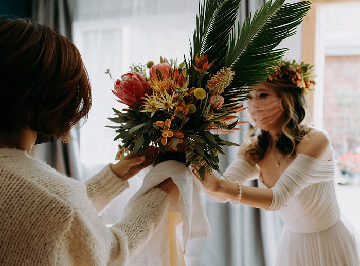 mom hands the tropical flower bouquet off to the beautiful bride