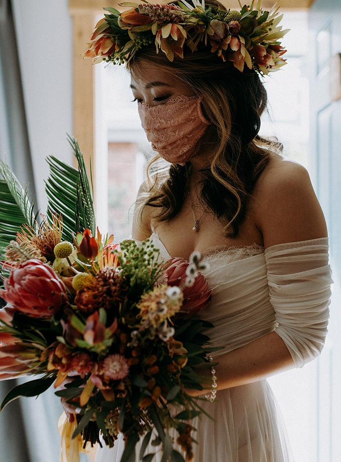 the bride holding her tropical flower bouquet with a tropical flower crown