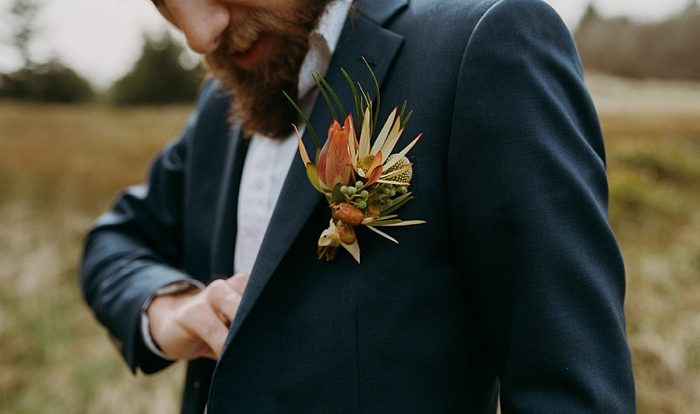 the groom's boutonniere as he reaches for his vows