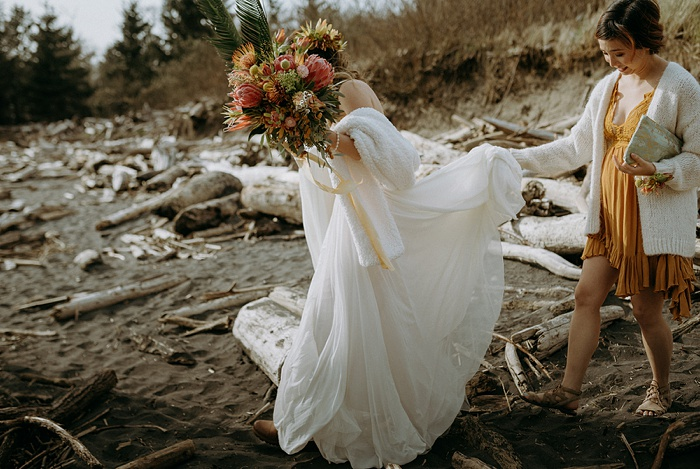 the bride and her sister trek through driftwood to head to the beach ceremony