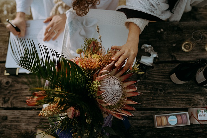 a wedding guest touches the protea in the tropical wedding bouquet