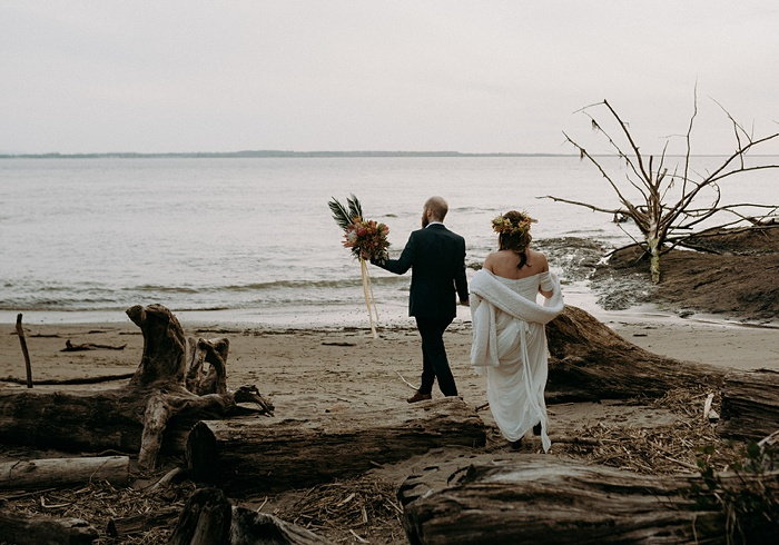 a newlywed couple walks along the beach holding the bouquet
