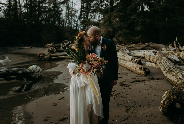 A couple kisses on the beach holding a tropical bouquet full of colorful flowers