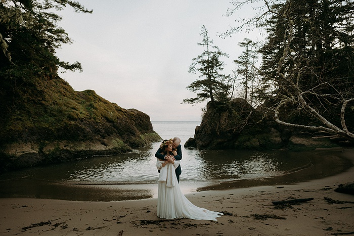 bride and groom embracing on the water surrounded by forest