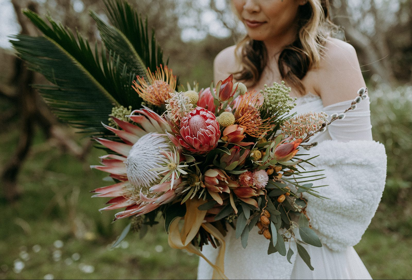 bride holding a wedding bouquet full of tropical flowers like protea, leucadendron, palm leaves, and grevillea