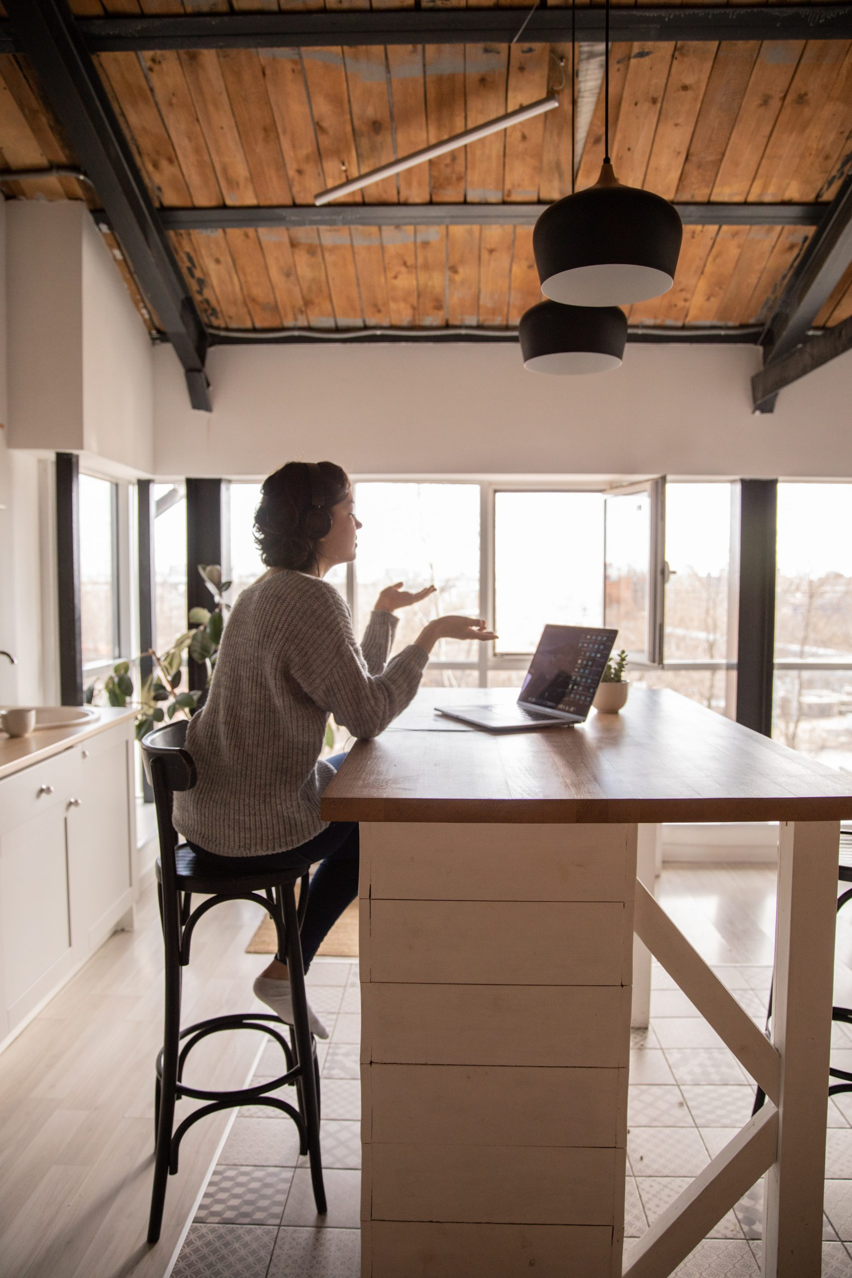 a woman having a conversation on her laptop in the kitchen