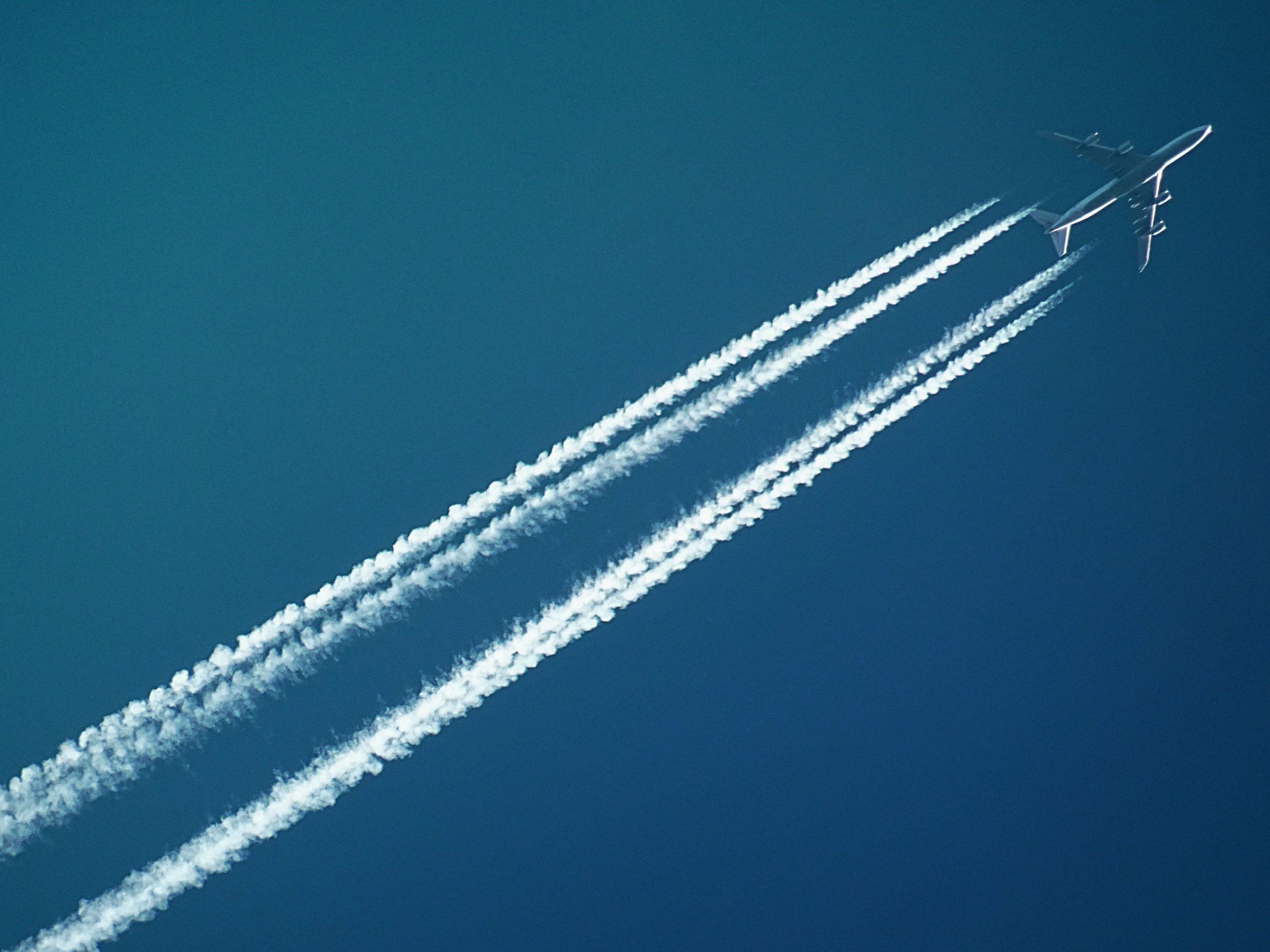 a plane flies across a blue sky with jet streams