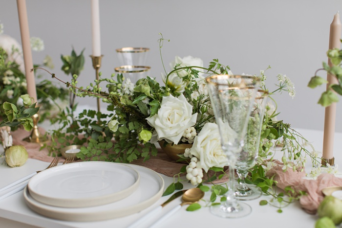 a table set with white stone plates, candles, and white floral centerpieces
