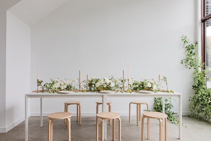a modern white space with a wedding head table, a floral installation, and big windows