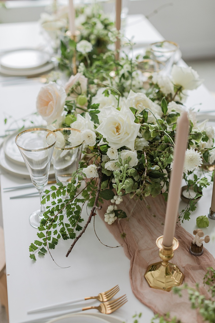 a table set with golden candlesticks, taupe candles, a table runner, and a white floral arrangement