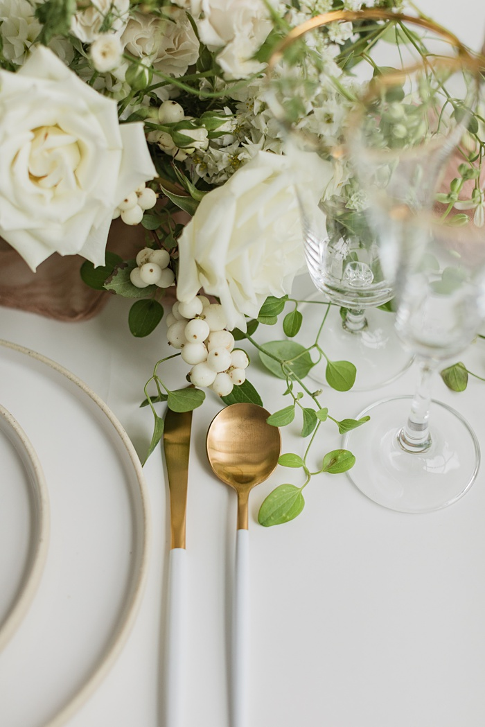 a table setting with gold flatware and a white floral arrangement