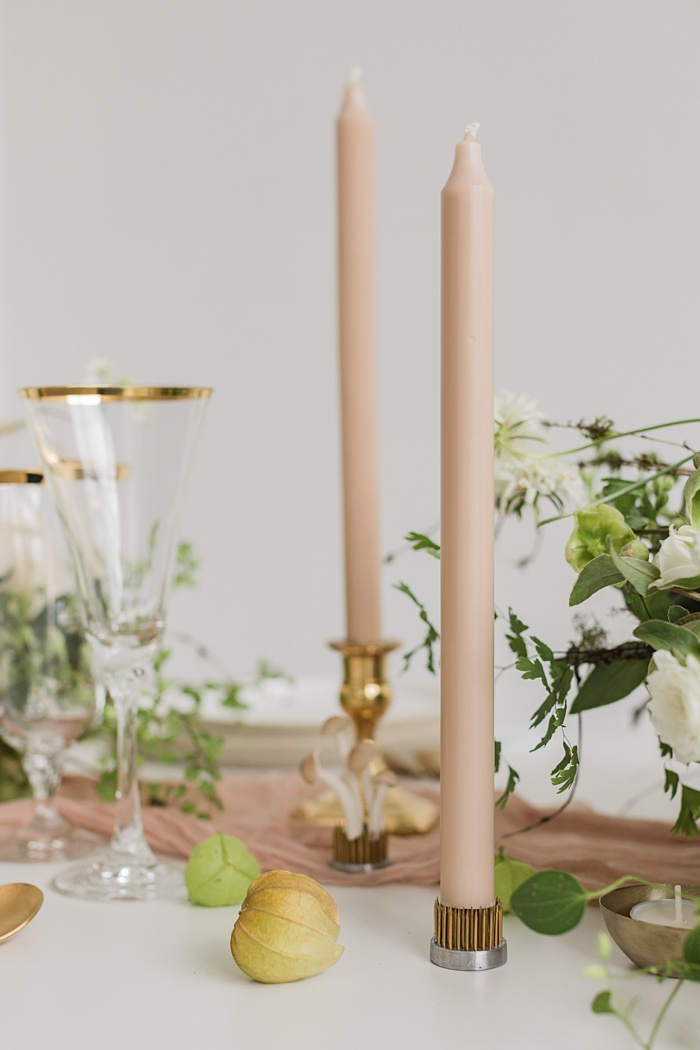 a table set with a neutral table runner and taupe candles, with tomatillos scattered on the table