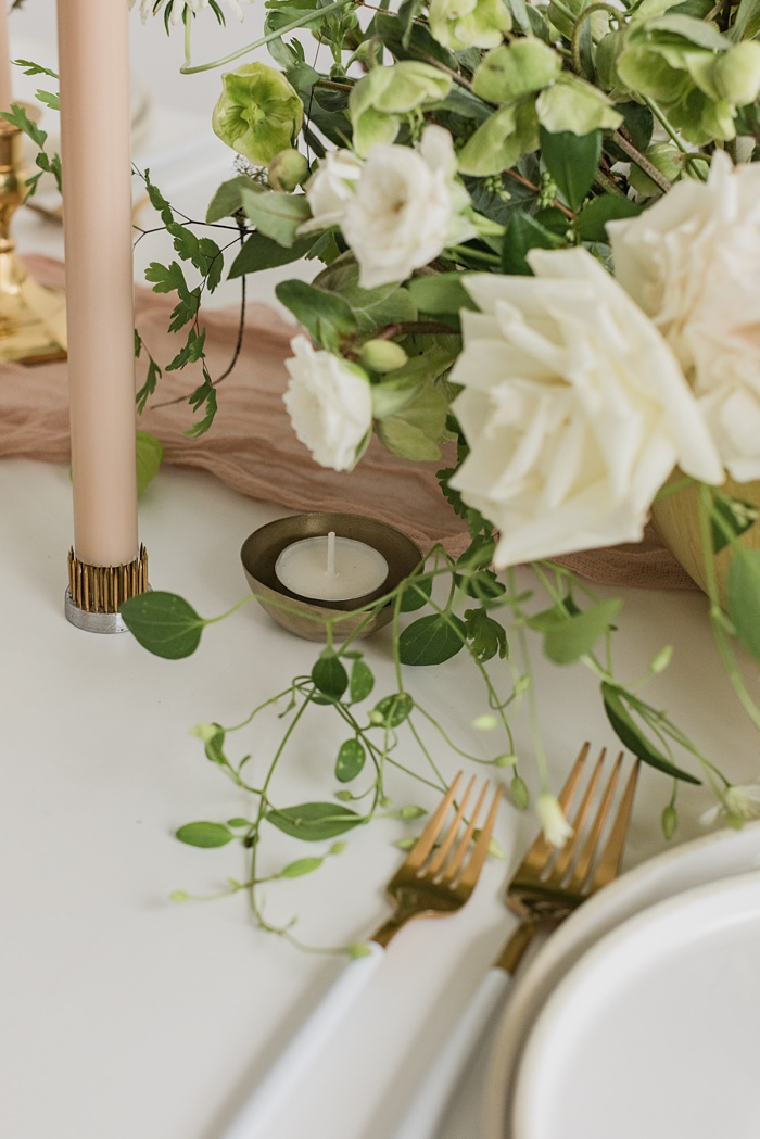 a tablescape with neutral table runner, candles, gold flatware, ceramic plates, and a lush white and green floral arrangement