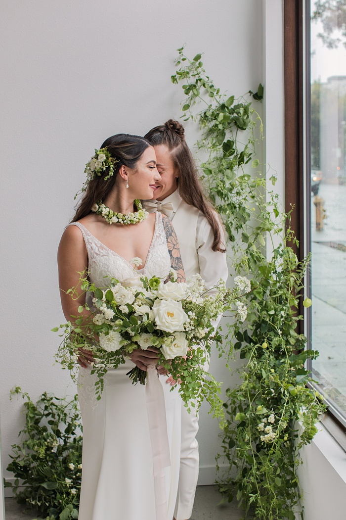 the brides embracing in front of a floral installation
