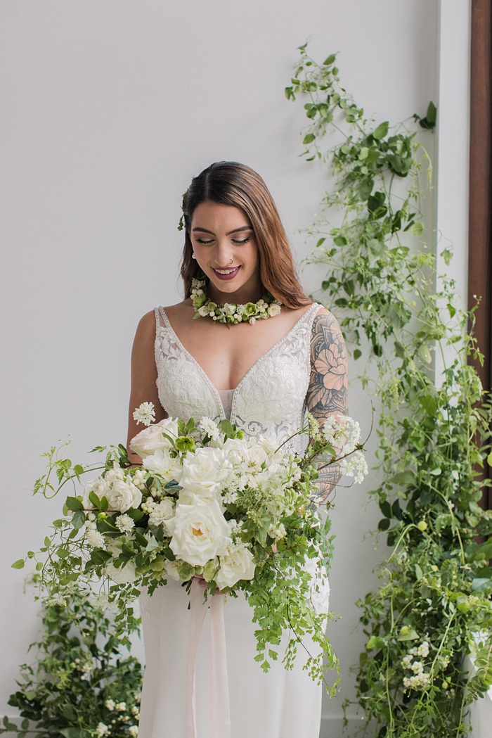 a bride holding a white wedding bouquet in front of a floral installation