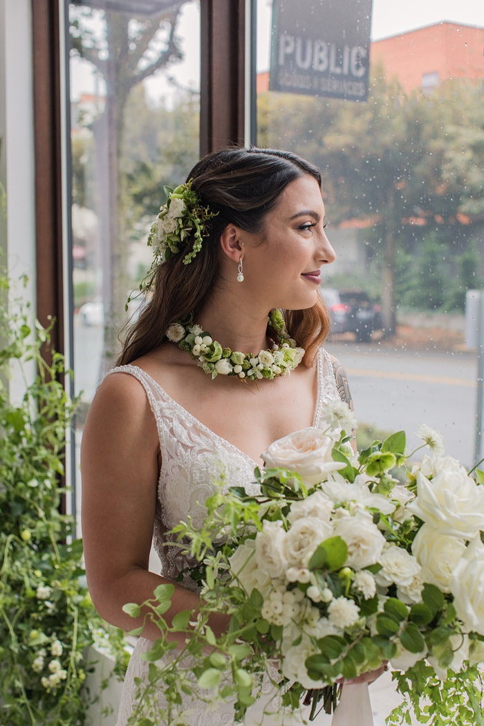 A bride looking out the window, holding her bouquet