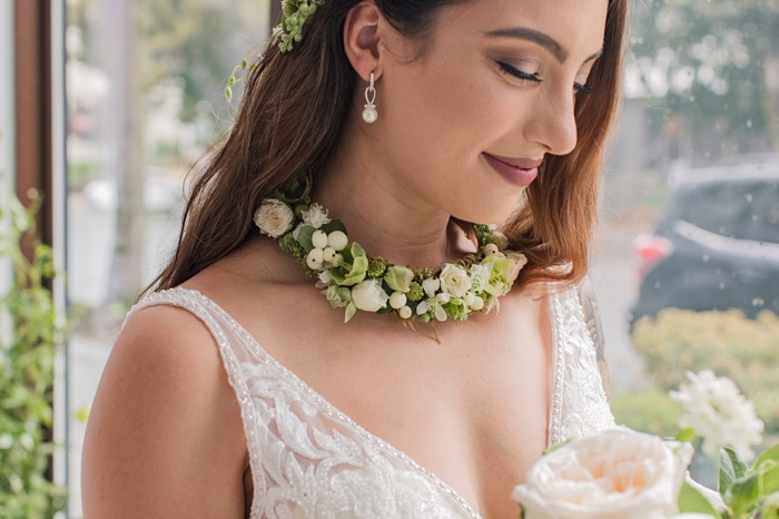 a bride looking down at her bouquet, wearing a white floral necklace