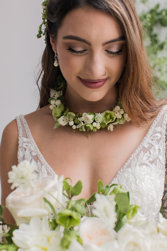 the bride wearing a floral necklace and holding a white bouquet