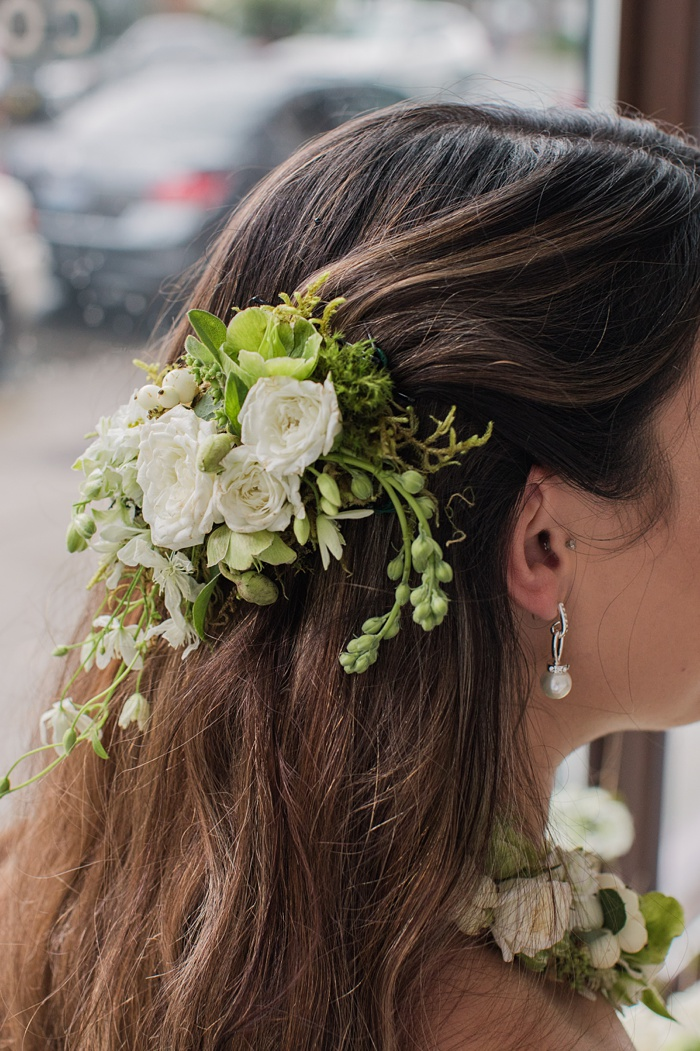 a floral hair piece with white and green flowers