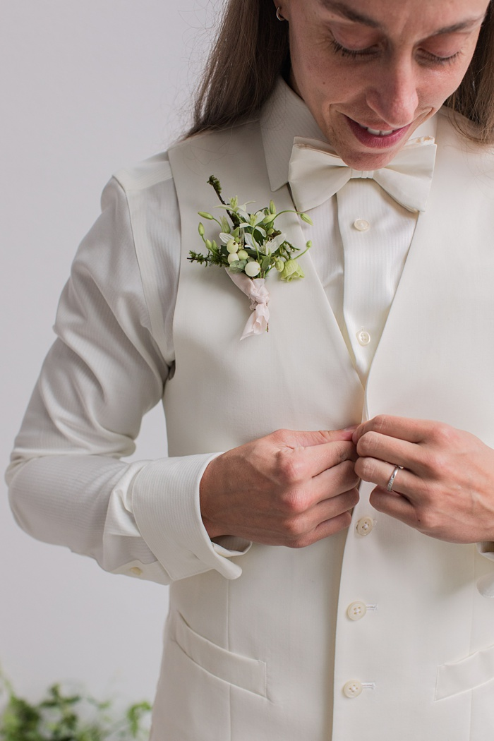 a bride buttoning her vest with a delicate boutonniere