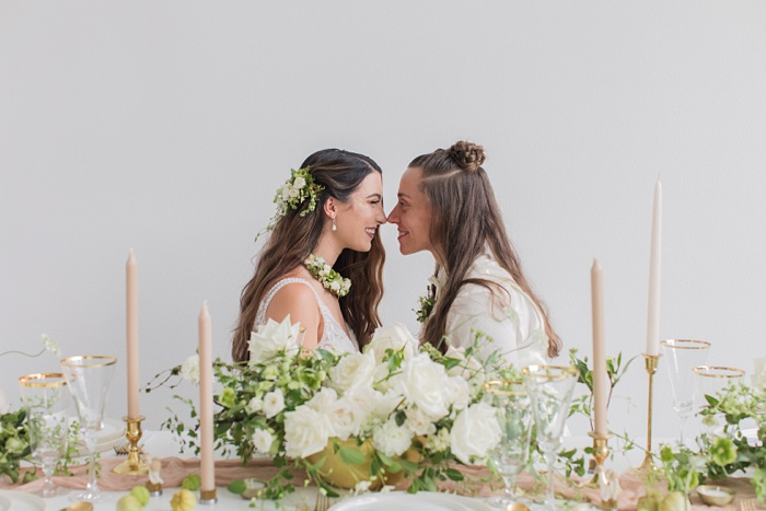 two brides touching noses at their wedding table