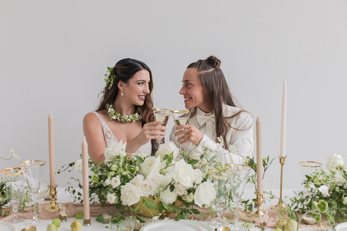 two brides toasting with champagne after their wedding