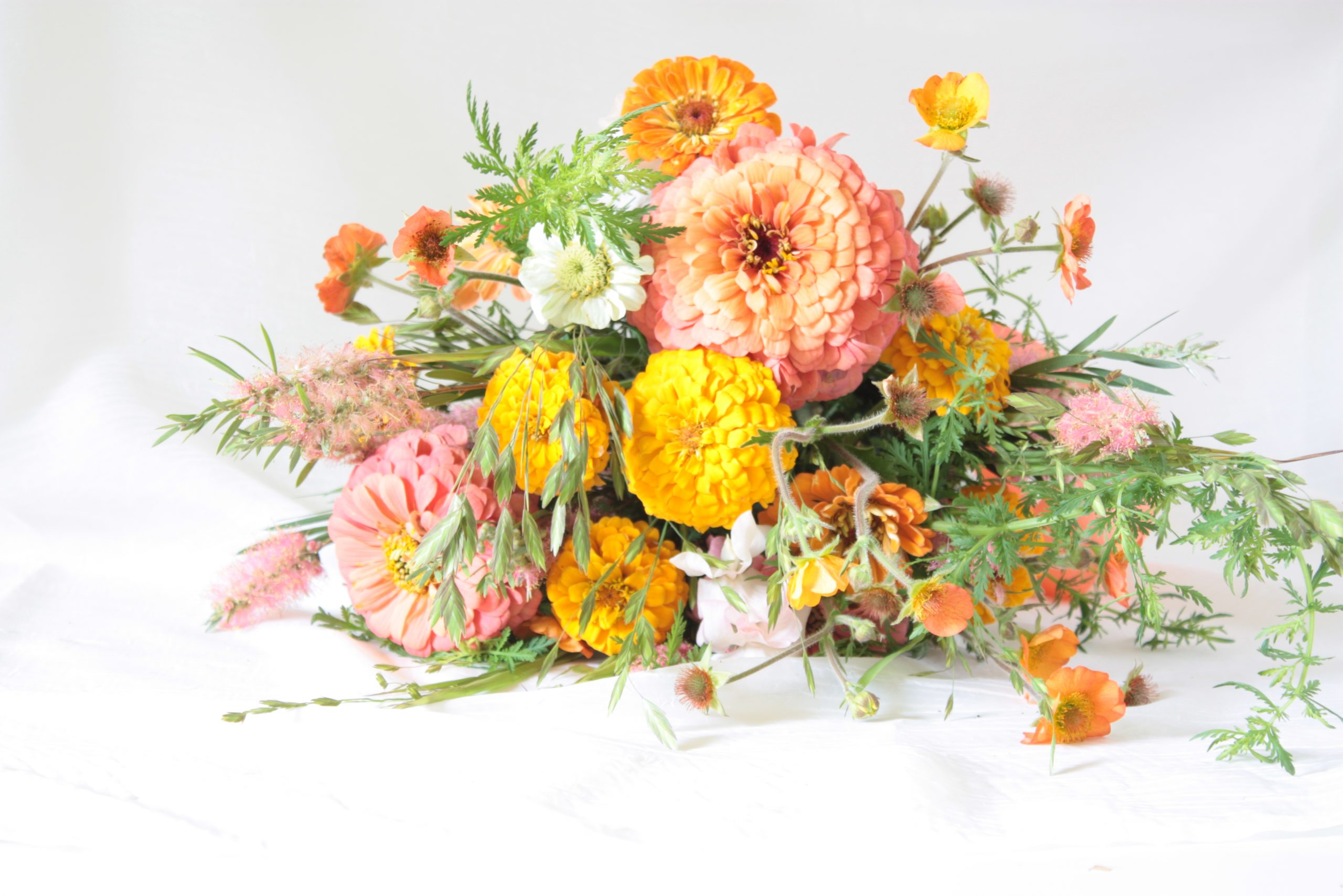 a bouquet of zinnias in peach, yellow, orange, and salmon colors, with goliage, grasses, and geum