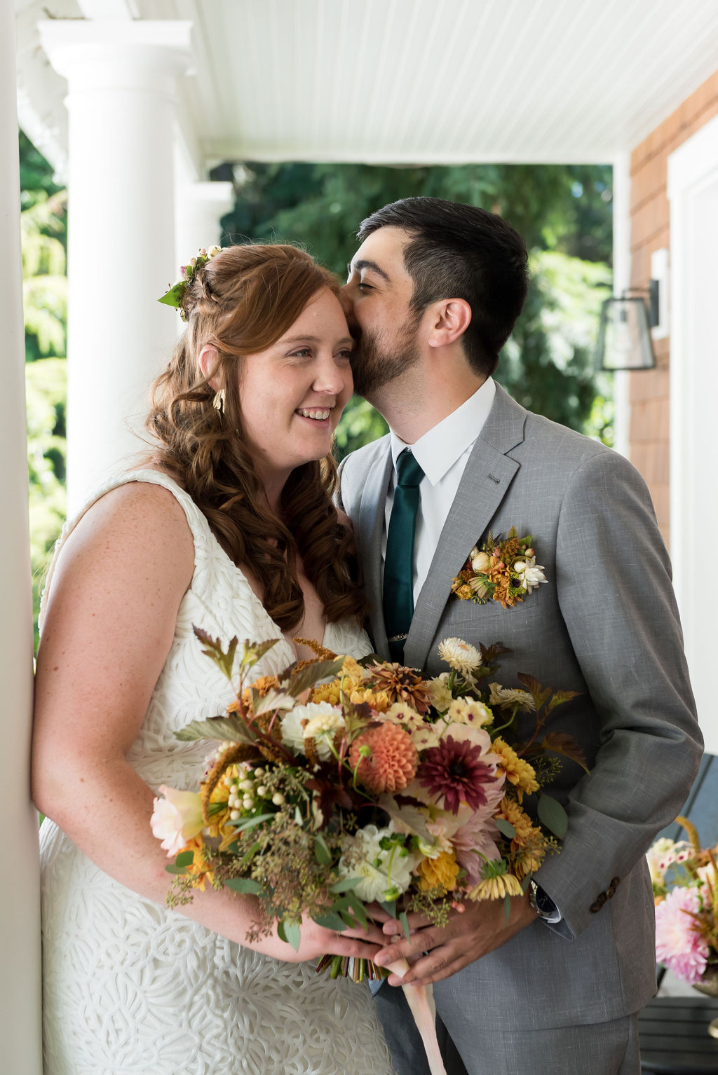 a bride and groom on a porch, holding a bouquet