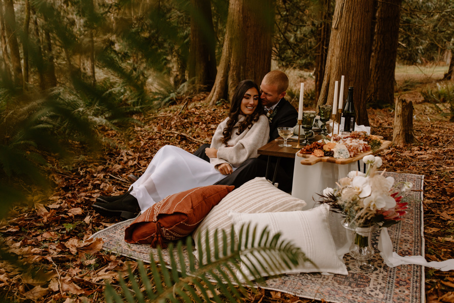 a couple sitting in the woods enjoying their elopement with a table of charcuterie